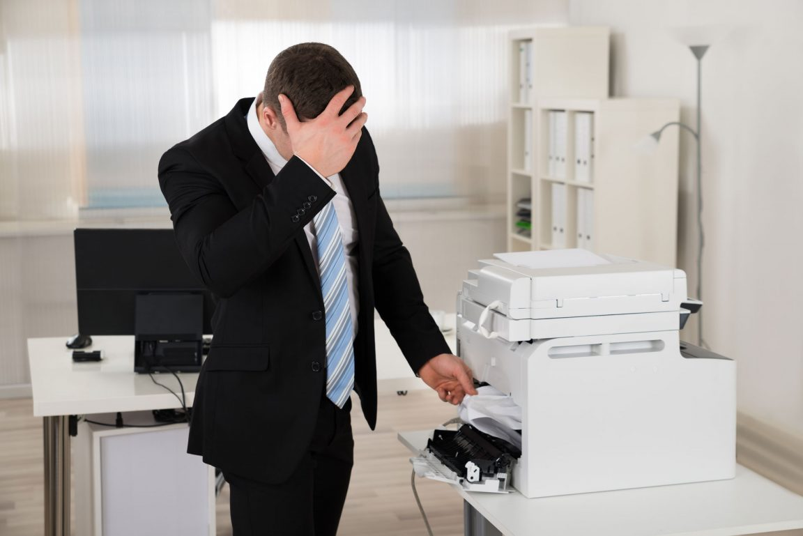 Frustrated business man dealing with printer issues